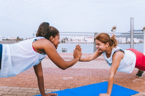 keeping fit couple high five-ing whilst doing press ups